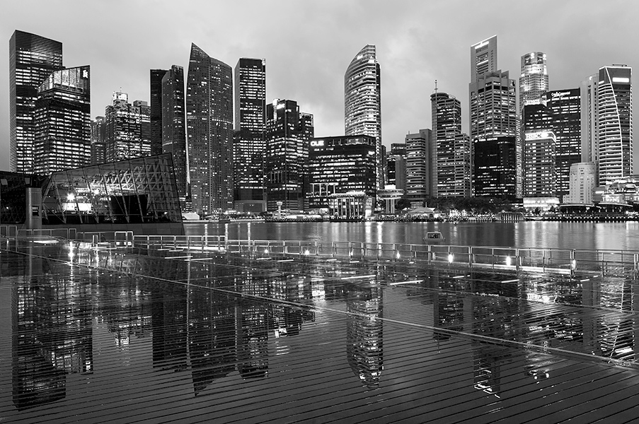 Photo for March 2013 (Duo Cities, Singapore)A rare posting of the concrete jungle, Singapore. I was out leading a workshop for a group of tertiary students when it poured. To their credit  no one was affected for long and went about shooting through the automated doors of the huge shopping mall. The doors were thus open due to our constant intrusion and that left the floor pretty wet. Fortunately, a big thanks to the alert cleaner who came to wipe it all dry and made my day when he smiled while I apologized.The rain did not however seem to stop until I saw a lady walking out without an umbrella! That was impossible and I followed suit and realised it was no longer raining. Waved the all-clear to everyone while I rushed to get into position. The magic hour was now and I had a 24 TSE ready to get the buildings straight up and composed with the reflection that was not a common sight. 3 shots later, the tourists started pouring out with built-in flashes blasting at the faraway buildings...Canon 5D Mark III, 24 TSE II,  Processed in Photoshop CS6.
