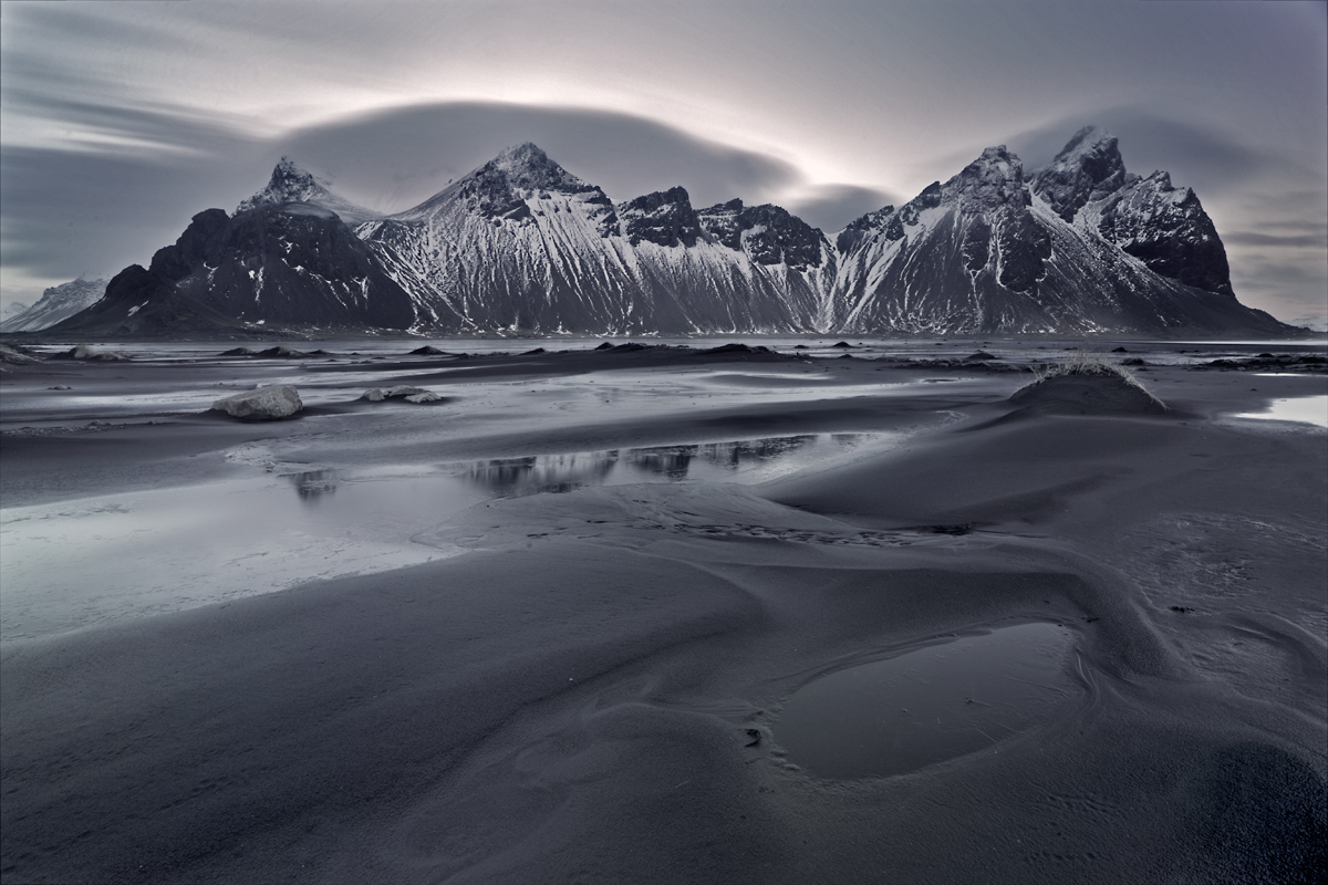 Photo of the Month January 2014 ( Majestic Vesturhorn )Iceland is an island with high volcanic activity, as a result, most sands in Iceland are black (lava sand). When we were photographing this area, we minimalise walking around to prevent footprints. If needed, we literally walk in each other's footprints. Shot in winter, crampons are still a neccessity as some sand have ice in them and some parts of the water are still frozen. This image was a difficult case to handle during post-production. The VND filter that was unwillingly stuck to the lens, had colour casts that was pretty bad in it. Some parts of the image had magenta , while the other has blue casts. A multitude of Color Balance adjustments layers and other adjustment layers finally got to the image I initially had in mind. This was how it felt, when I was capturing the sand dunes with the majestic Vesturhorn Mountain at the back. Shot with Canon 6D, 16-35mm II with a Variable ND Filter for a long exposure of the clouds.