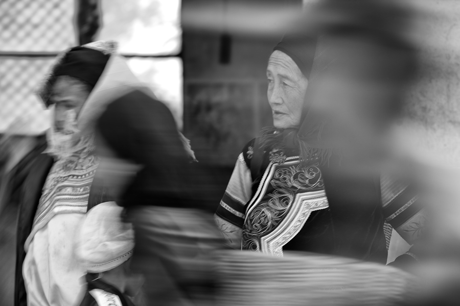 While keeping my focus locked on the elderly lady across the road, the slow shutter speed blurred the movement of the pedestrians. Rendering them as a foreground element, they do not distract from the women clad in their traditional costumes.