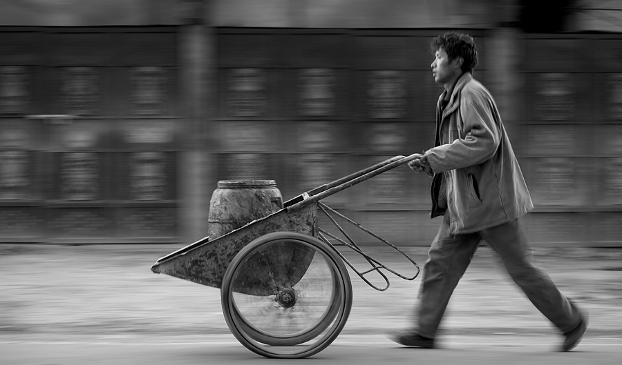 The man was not really pushing the cart that fast but a slow shutter speed combined with panning along with him gave the impression. Other than giving him that extra speed boost, panning with a slow shutter speed can also blur out what would have been a distracting background.