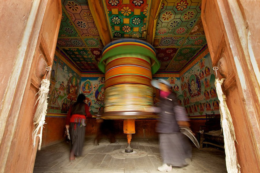 A smile, nod and a wave from an elderly man brought me to the small closed door. Not knowing what was inside, I was curious and accepted his invitation to step forward. When the opened doors presented the prayer wheel, I was left in awe and the devotees stepped in for their daily ritual. I remained outside and laid down on the ground with a wide angle lens to get the entire scene in.