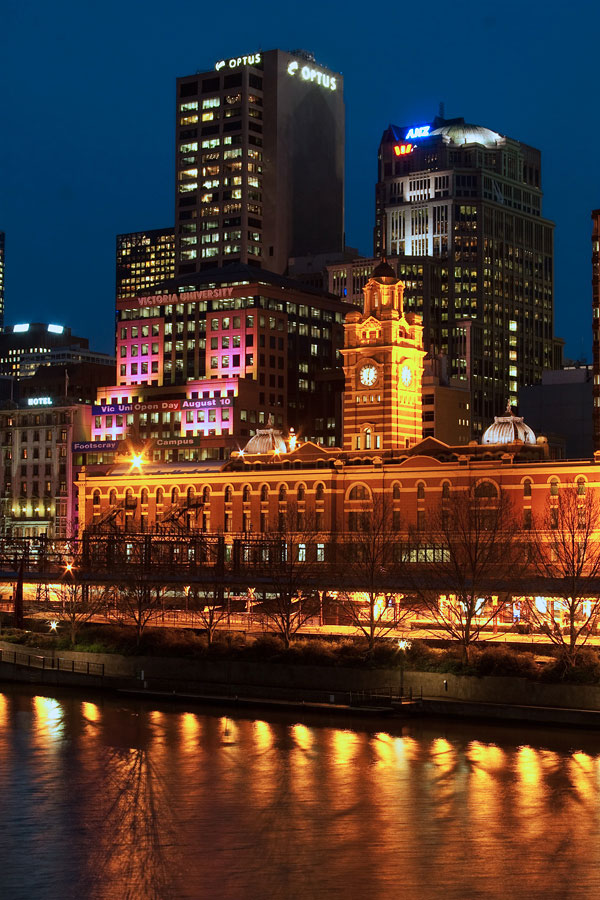 A blue sky offsets the warm lighting from the Flinders St. Station in Melbourne. A slow shutter speed blurred the water just so slightly.