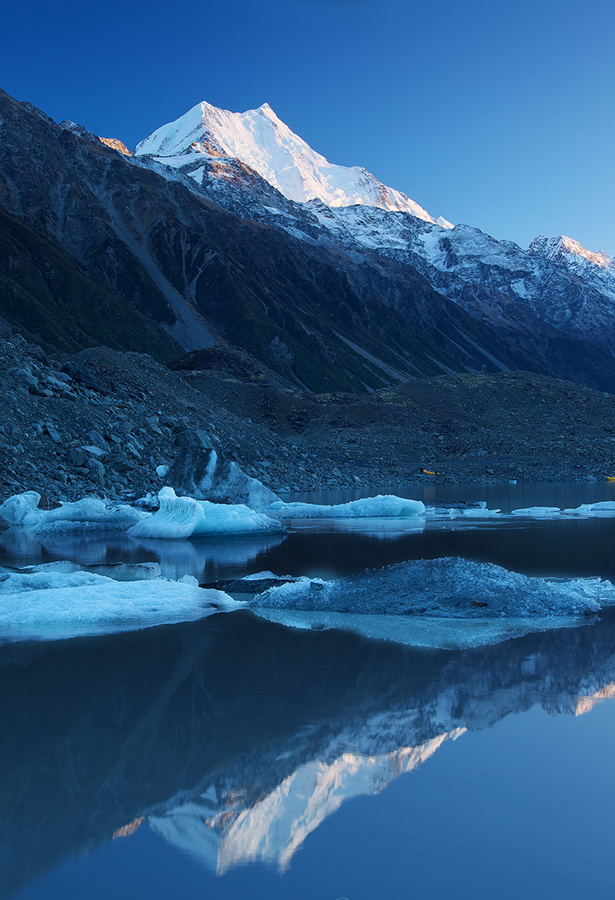Tasman Lake, a location where the peak of Mount Cook could be seen not just at the top of the frame but at the bottom where the glacial waters hold her reflection.
