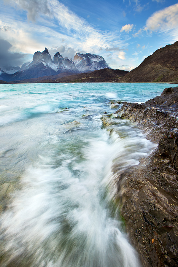 Photo for May 2012: Crashing PaineI could no longer feel the ground with my numb legs. The freezing waters, constant spray and high winds was constantly threatening to put my sunset shoot to a premature end. Welcome to Torres Del Paine National Park, Chile.A early morning recce located this shoreline that lined up nicely with the mountains in the background. With the iPhone as a scouting camera, I determined my angle and headed back in the evening. A pity there was a lack of light on the peaks but the experience was still an unforgetable one.Canon EOS 5D Mark II w/ Canon 16-35 L, processed in Aperture and Photoshop.