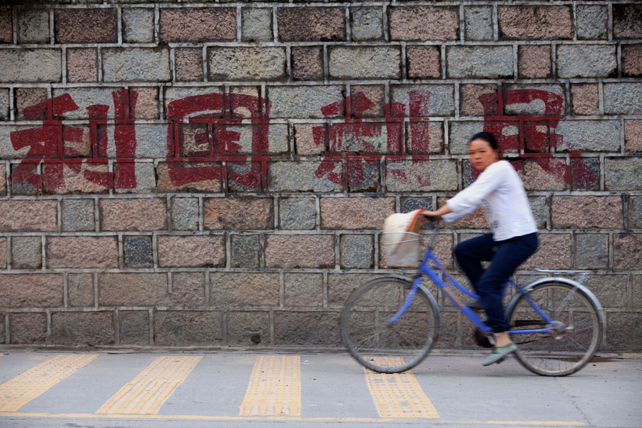 A lady rides past a wall bearing the words, {quote}For the country, for the people.{quote} It was most probably painted on during the Cultural Revolution and serves as a reminder to the Chinese people then.