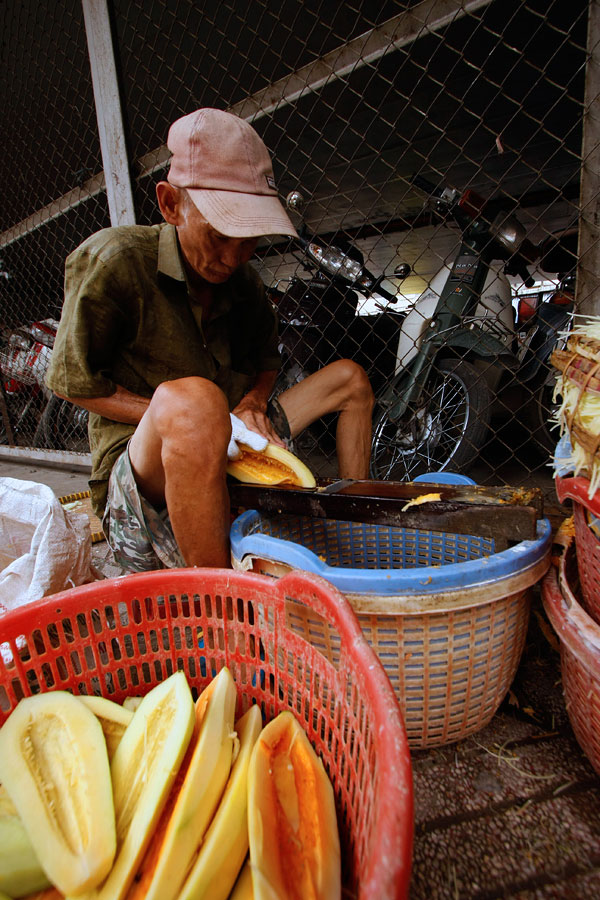 This man was working at an amazing rate and the skins were coming off the fruit at an alarming pace. When the red basket was filled and he moved it forward, I stepped in, used it as a foreground and got the shot.