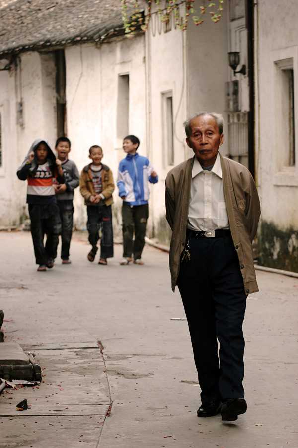 I try as much as possible to get out of the main streets when I travel. Quite frequently, the back alleys are where you will really see the way of life of the local people. These group of boys were getting excited when I lifted up my camera. The elderly man however was not bothered at all.