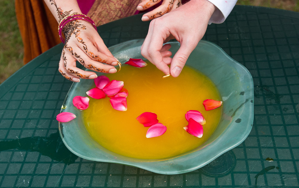 A bride and groom prepare to drop their wedding rings into a bowl during a henna party in Minneapolis, Minnesota