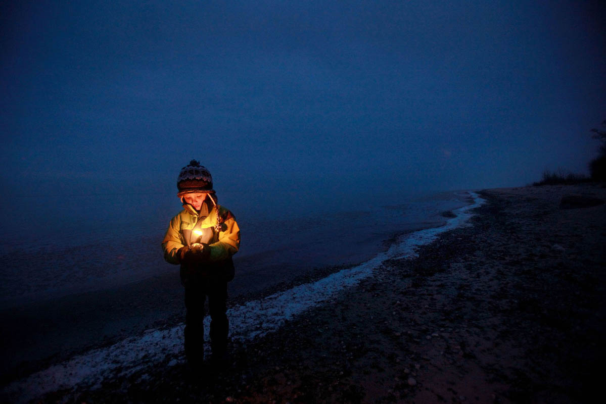 Benjamin Picciolo, 4, holds a candle as he awaits the sunrise on the shores of Lake Michigan to celebrate the winter solstice.