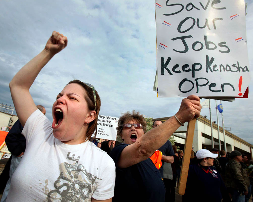 Latisha Repinski of Kenosha (left) calls to cars to honk their horns in support, while picketing with her grandmother Barbara Repinski at the Chrysler Engine Plant in Kenosha. Barbara Repinski has worked at the plant for 30 years. Workers and community members picketed outside the plant, urging Chrysler to reconsider restructuring the plant instead of closing it and expanding a facility in Mexico.