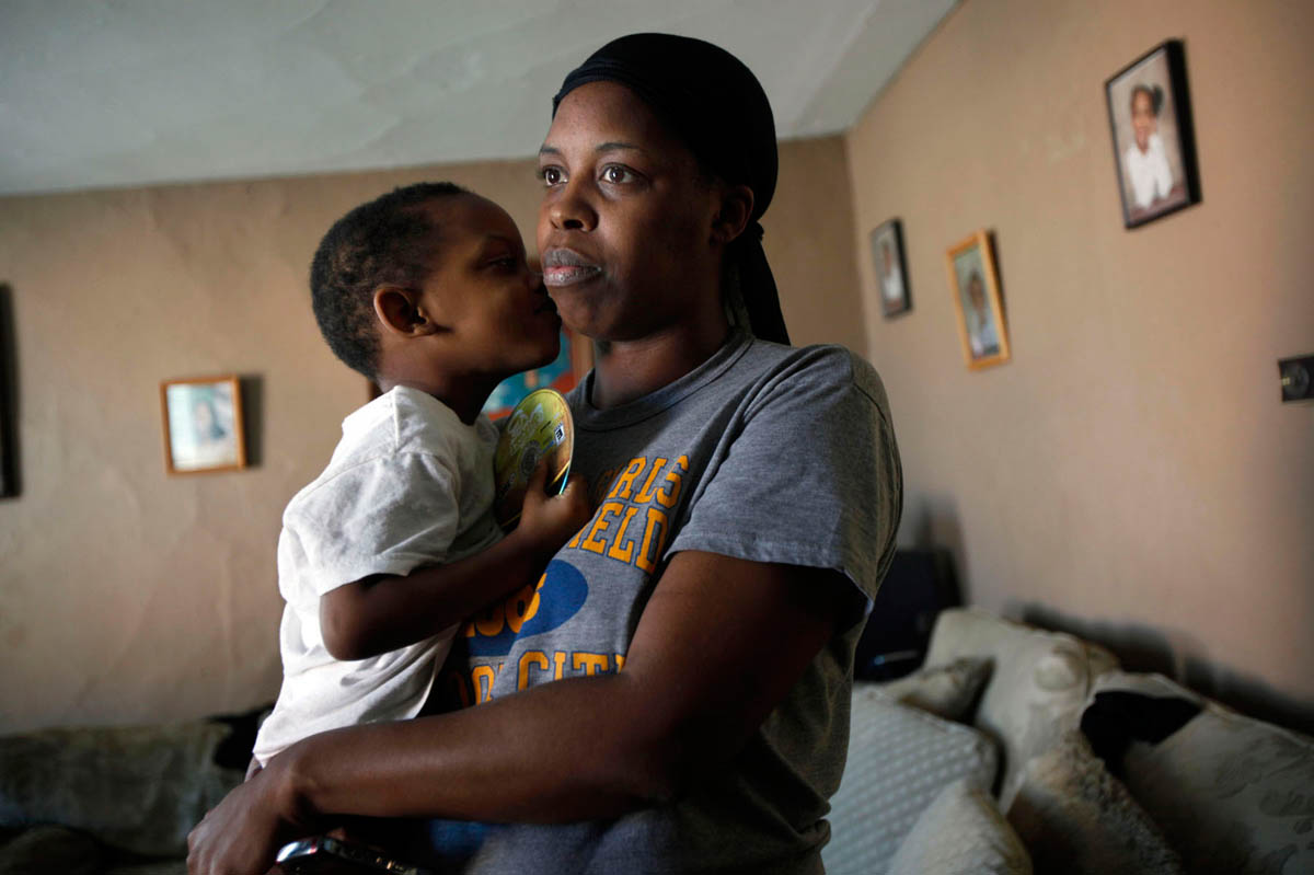 Crystal Welsh holds her son Kimathi Burrows, 3, in their Milwaukee home. A strong turpentine smell plagues the neighborhood and the house where Welsh lives with her six children is in a high crime area. She believes the smell has one of her children to become ill but she is unable to secure a financial stability needed to move her family to a better place.