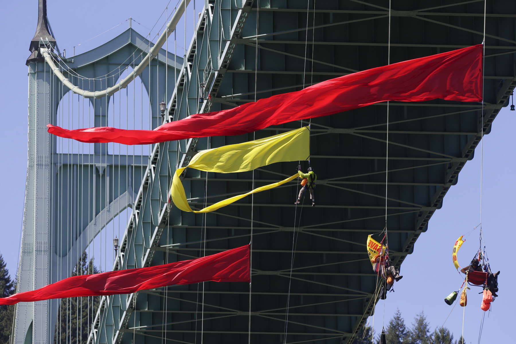 Greenpeace activists hang off the St Johns Bridge over the Willamette River to protest Shell Oil's drilling in the Arctic and attempt to prevent one of Shell's ships from heading to sea.
