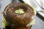 A smoked salmon bagel sandwich at Nuvrei in Portland, with toasted poppy seed bagel with cucumber, dill, red onion chive cream cheese and butter lettuce.