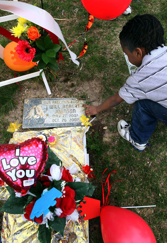 T-Mor Hendrix, places a cupcake on the headstone of his half-brother Will Robert Johnson as the family celebrates the dead child's birthday.
