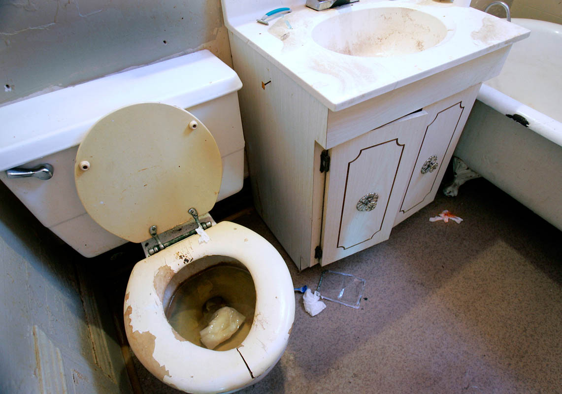 Four tenants share this bathroom at a boarding house in Milwaukee, all with severe mental illness. The landlord does not maintain the facility, leaving the bathroom unclean with a razor and bloody tissue lying on the floor. Six of the landlord's tenants have died in her 16 years of business and the City of Milwaukee continues to house clients at her facilities.