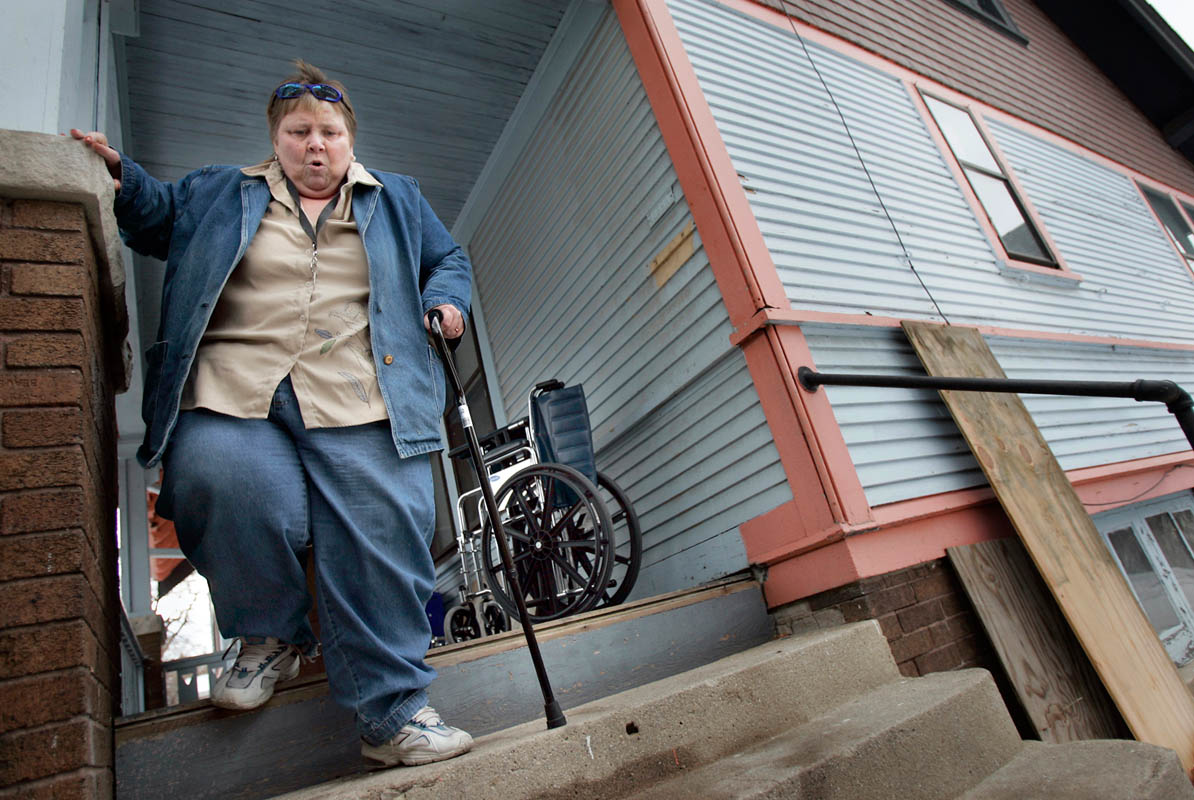 In addition to Georgia Rawlings's schizophrenia, she is plagued by poor physical health. The Milwaukee woman has difficulty walking, and grasps the wall for support as she tries to navigate the steps to her Milwaukee home. She was lucky to find a home to rent on her limited income but struggles to live in a facility that is non-ADA compliant.
