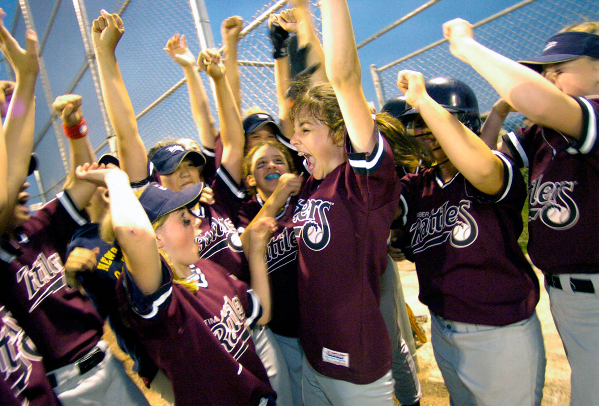 Timber Rattler's Kenlyn Bauer (center) cheers with her teammates after winning the Appleton City Softball Tournament for 11-12 year old division.