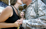 Saharra Lane, 9, of Manawa, watches eagerly as her parents kiss upon the return of her father, Allen Lane, from Iraq. Allen served with the Army National Guard's 1st Battalion, 121st Field Artillery and was deployed for 14-months.