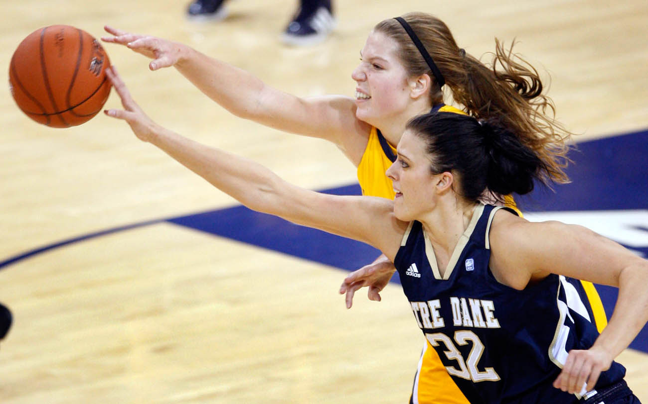Marquette's Katherine Plouffe (left) and Notre Dame's Becca Bruszewski  sprint to gain control of the ball after Plouffe fumbled it during the first half of the game at the Al McGuire Center in Milwaukee.