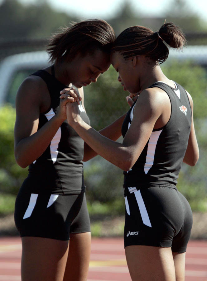Riverside High School students Mariah Robinson-Page, 15 (left) and Demetra Camble, 15, hold hands as they say a prayer before running the 4x2 relay at the City Conference meet.
