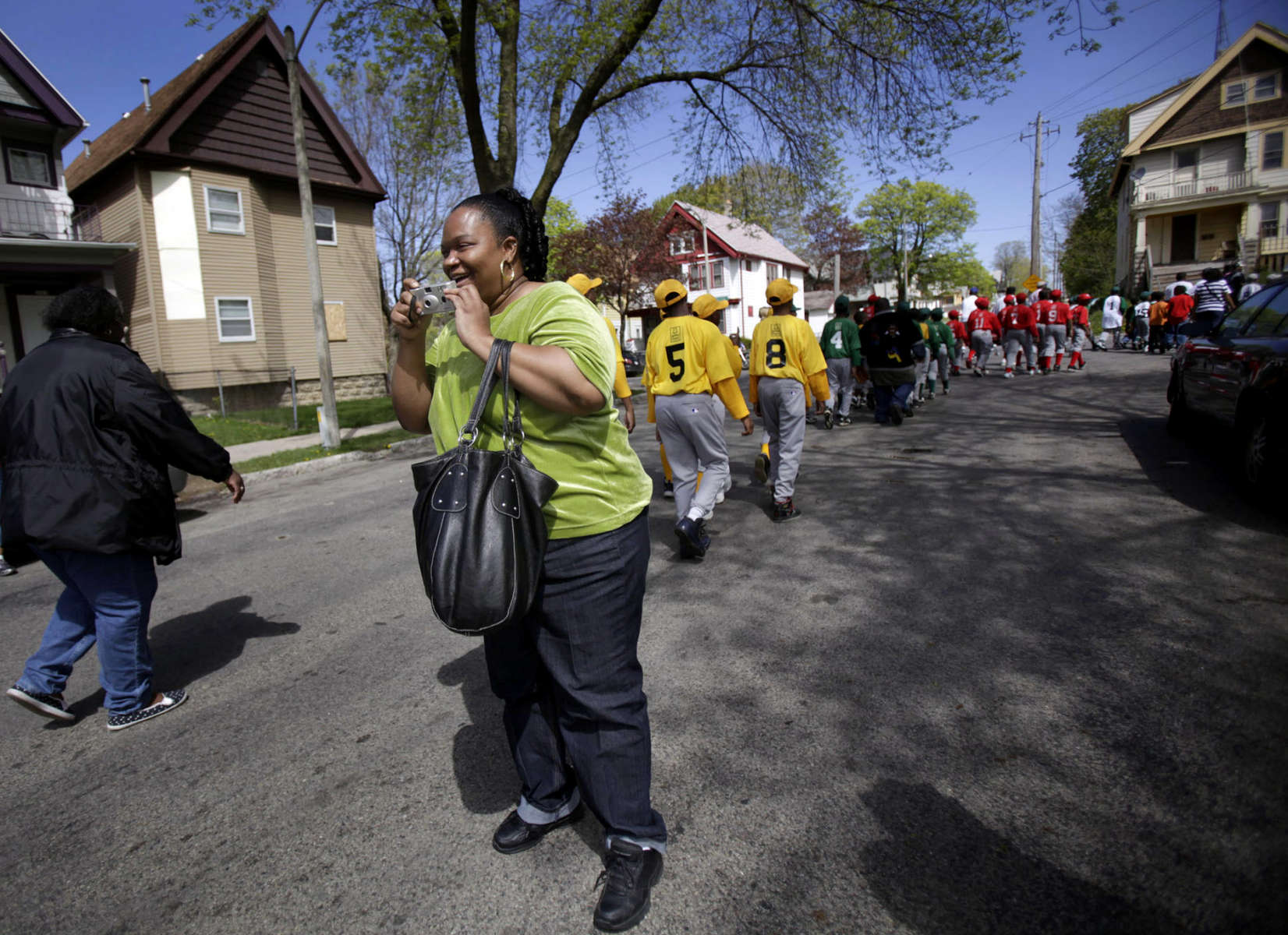 To help the boys meet other children from their neighborhood, Brandy has signed them up for local Little League. On opening day she searches the crowd for her two sons, proudly snapping photos of them as they march by with their Little League team during a parade.