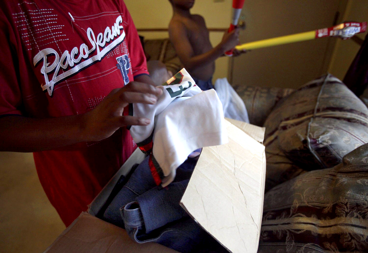 Tae, 12, unpacks his belonging from a cardboard box, which include a Milwaukee Bucks jersey that he has long outgrown. Shakiem, 10, checks out a new whiffle ball set sent from his foster family.