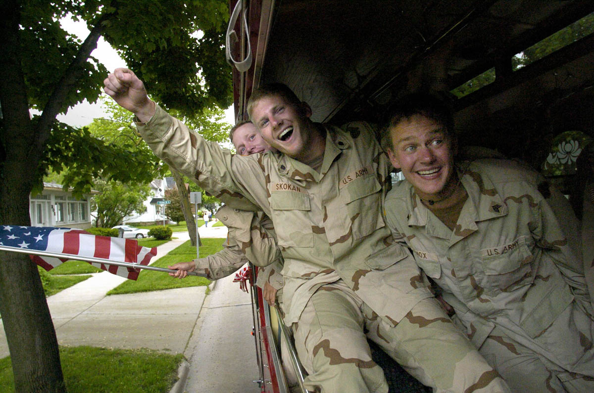 Members of the Army Reserve's 395th Ordnance Company Spc. Chris Skokan, (center) and Sgt. Josh Knox, cheer as they are escorted through Appleton, Wis.  The unit had been deployed 10-months ago in support of Operation Enduring Freedom.