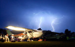 Friends stay dry under the wing of Dan Nelson's 1961 Cessna 172 as lightning strikes and the storms hit the EAA AirVenture in Oshkosh, Wis.