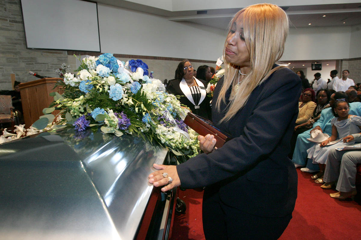 Angela Virginia can't bring herself to say goodbye to her son and oldest child, Purvis, 12, at the conclusion of his funeral service. Purvis and a friend were missing for a month before their bodies were discovered in a pond at the park.