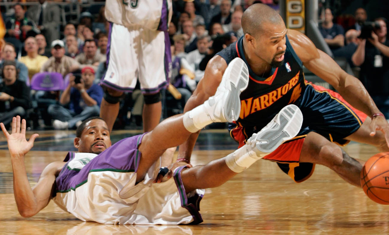 Milwaukee Bucks' Charlie Bell, left, and Golden State's Derek Fisher, right, collide as they chase down a ball.