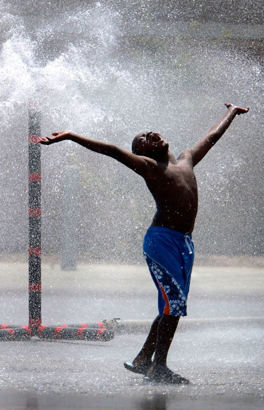 Machio Childress, 7, is ecstatic to play in the water at a cool spot during a heat wave in Milwaukee, Wis. Designated cool spots throughout the city were set up by area fire departments by using a large sprinkler attached to a fire hydrant to provide relief from the heat.