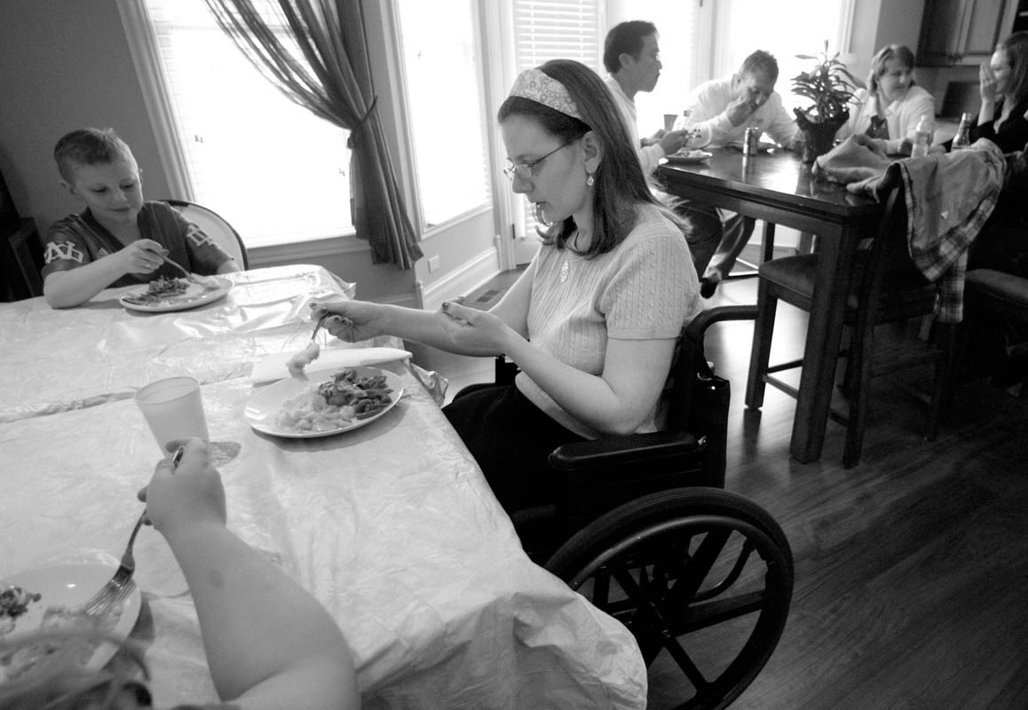 Courtney pokes at her food during Easter dinner. She is seated with her nieces and nephews at the children's table, her back turned to the adults.