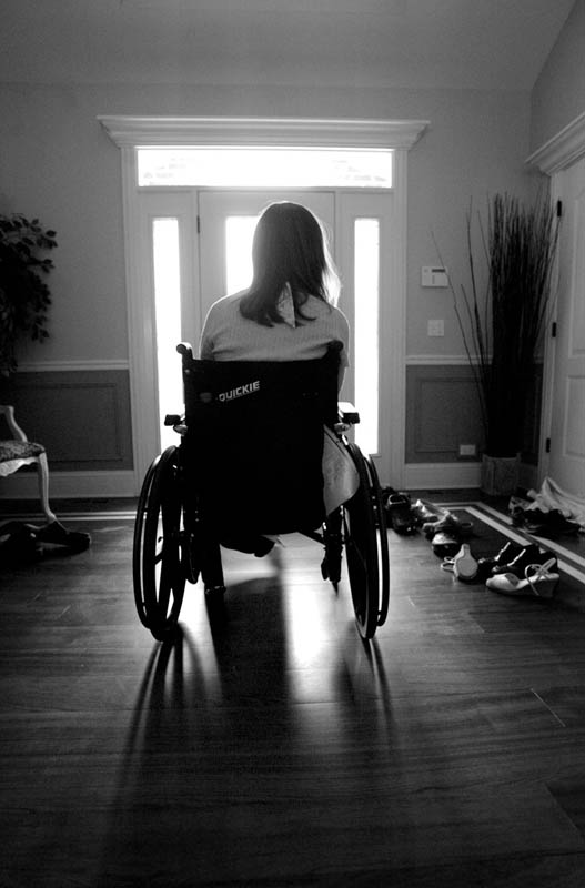 Courtney stares out the front door, alone in the hallway, after wheeling herself away from a family dinner. One aspect of Courtney's brain injury is intense frustration and quick mood changes that cause her to become very angry or solemn.