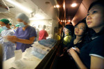 A group of donors from Hong Kong peer through the viewing window into the operating theater aboard the ORBIS Flying Eye Hospital in Phnom Penh, Cambodia, December 13, 2007.