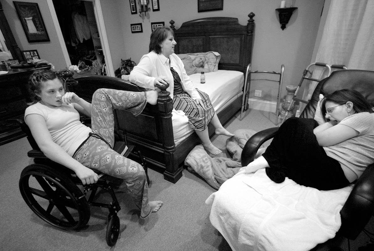 Brittney Henrie, 12, left, her mother Juli, center left, and sister-in-law Angie Johnson, center right, are exhausted after a full day of caring for Courtney. They have spent the past 45 minutes trying to convince Courtney to take her evening medication and must sit out her stubborn mood.