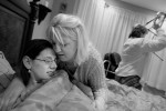 Courtney is tucked into bed by her sister-in-law Angie Johnson, center, as Juli picks up Courtney's room and prepares for another day.