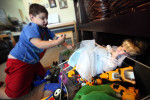 Izzy rummages through a toy box April 21 at the family's Monona home, searching for Batman. Toys such as the dolls favored by Izzy's older sisters were are cast aside for trucks, guns and superheros.