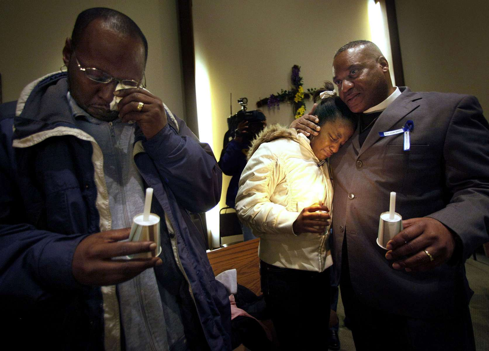 Kenny McClellan, grandfather to 13-month-old Christopher Thomas, Jr., (left) wipes his tears as his daughter Shantrina Freeman, 12, (center) is comforted by minister Gregory Lewis, (right) following a candlelight vigil held for Christopher Thomas, Jr. The toddler was placed in the home of his aunt Crystal Keith, by the Bureau of Milwaukee Child Welfare. Signs of violent child abuse were not recognized by the caseworker, and Thomas died of injuries after a severe beating by his aunt.