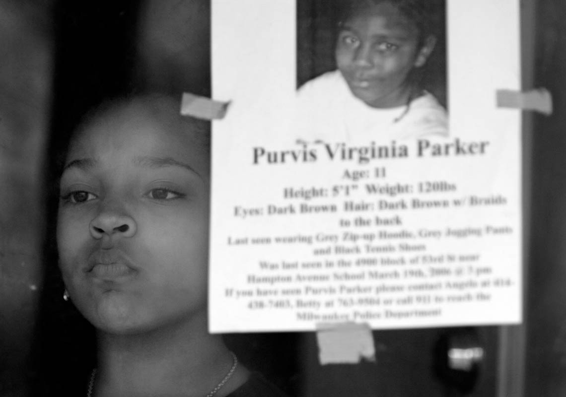 Shymeka Brown, 9, watches out the front door of her Milwaukee home as her mother gives a television interview, regarding her missing brother, Purvis Virginia Parker, 11. Parker and his neighborhood friend Quadrevion Henning, 12, were last seen Sunday at 3:30 p.m. playing basketball in the area.