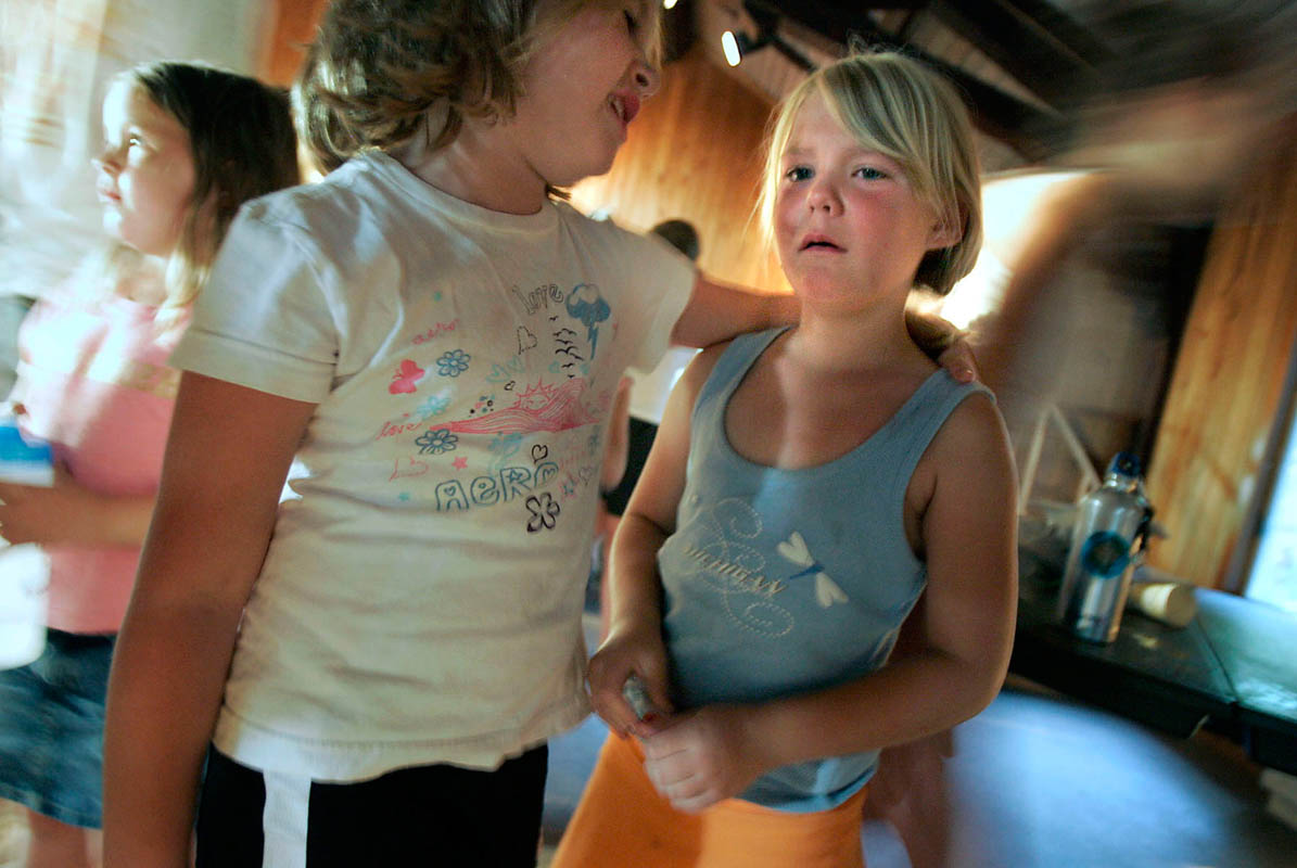 Megan Butala, 7, of Rice Lake, WI, is comforted by a cabin-mate as she cries following a discussion about what it's like in Iraq. Her father was deployed to Iraq and returned in November, but she still has great difficulty in separated from him. About 25% of returning troops have been diagnosed or have symptoms consistent with the disorder. A child whose parent has post-traumatic stress disorder often will mimic the symptoms, experts say.