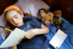 Veronica Sherman,9, of DeKalb, IL, writes her father a letter, with her camouflage bear wearing dog tags nearby. The bear was a gift from her father before he deployed to Iraq and it's never far from Veronica's hands.