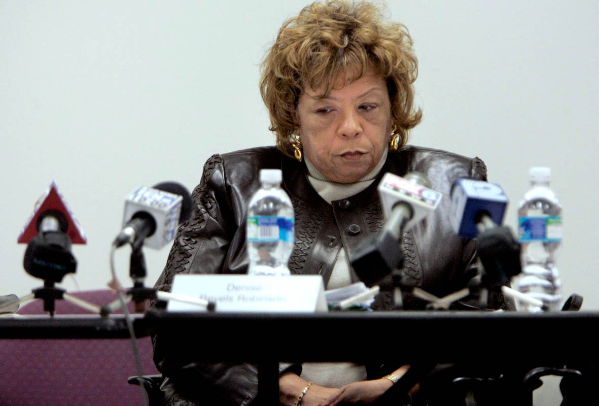 Denise Revels Robinson, director of the Bureau of Milwaukee Child Welfare, sits surrounded by microphones at an emergency meeting of the Milwaukee Child Welfare Partnership Council. Robinson stepped down from her position following the ensuing investigation into Christopher's death which showed a complete breakdown of social worker protocols.