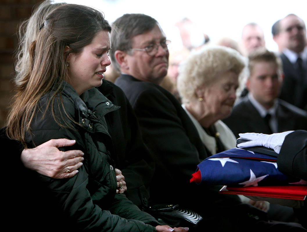 Kristen is reluctant to receive the folded flag from her husband's casket and a Purple Heart, at his interment ceremony at the Southern Wisconsin Veterans Memorial Cemetery in Union Grove. She thinks that losing a loved one on a far-off battlefield is something that happens in the movies, not something that happens to her.