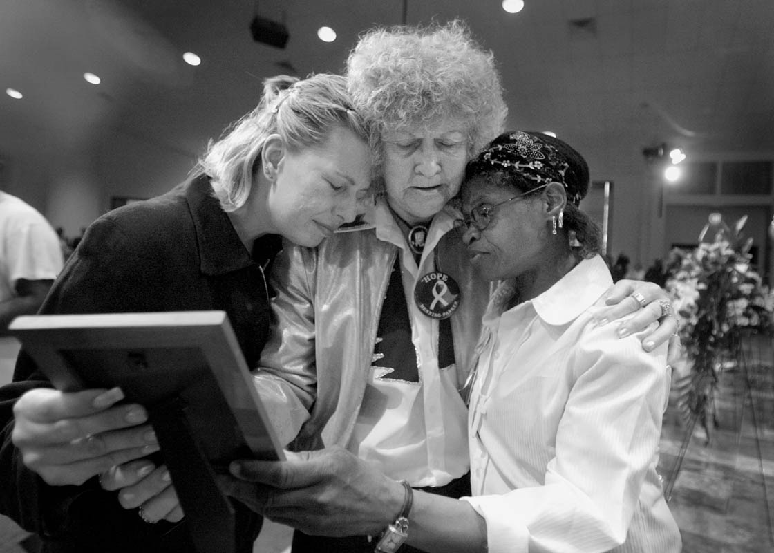 Susi Mayer, left, Natchlyn Voegtline, center, and Mary Whitaker comfort one another while holding a photo of Quadrevion Henning at his funeral services, April 20, 2006. The three women never met the boy, but met during their volunteer efforts to find him.