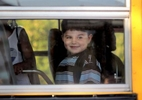 Izzy boards a school bus on his first day of school, smiling out the window at his mother. Jennifer has signed the child up as a male, and has been working with the school district to educate them on transgender issues and been very happy with the reception so far.