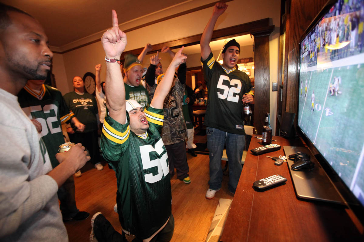 Jose Heredia (on knees) of Milwaukee hosted a huge party at his home and celebrates a sack during the third quarter of the Superbowl. This is the 16th party Heredia has hosted at his home.
