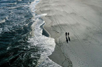 An aerial view of a couple walking on the sand by the ocean of Long Beach on April 22, 2020 in Long Beach, New York.  The boardwalk has remained closed since March 27 due to the coronavirus COVID-19 pandemic.The World Health Organization declared coronavirus (COVID-19) a global pandemic on March 11th.