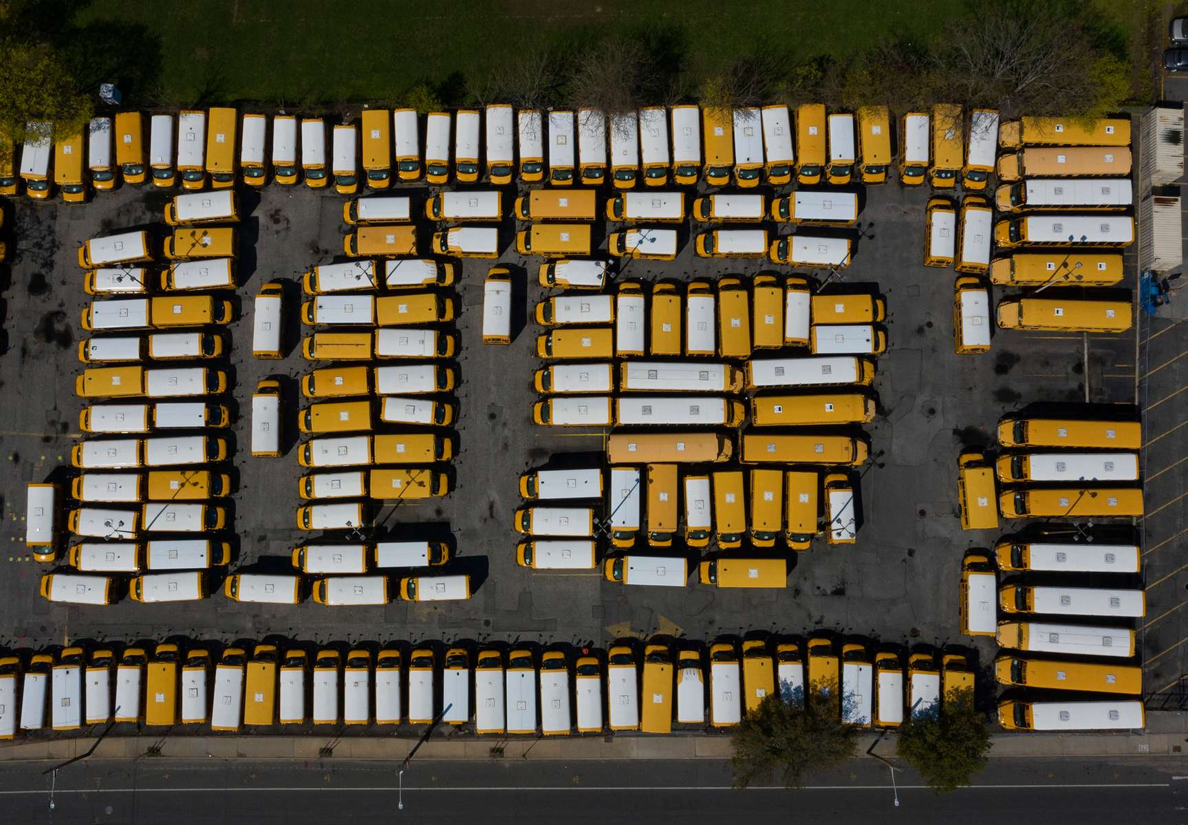 An aerial view of parked school buses in a parking lot bus depot on April 25, 2020 in Freeport, New York. Freeport schools have been closed since March 16th because of the coronavirus pandemic.