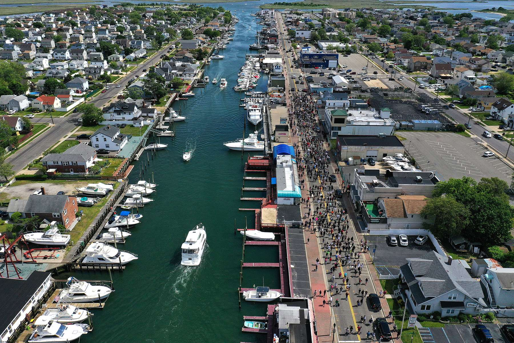 An aerial view of Protesters marching along the Nautical Mile on June 07, 2020 in Freeport, New York.  Minneapolis Police officer Derek Chauvin was filmed kneeling on George Floyd's neck, who was later pronounced dead at a local hospital. Chauvin has been charged with second-degree murder and three other officers who participated in the arrest have been charged with aiding and abetting second-degree murder. Floyd's death, the most recent in a series of deaths of black Americans by the police, has set off days and nights of protests across the country.