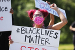 A Protester holds a sign during a gathering at Brentwood State Park to protest the recent death of George Floyd on May 30, 2020 in Brentwood, New York.  Minneapolis Police officer Derek Chauvin was filmed kneeling on George Floyd's neck. Floyd was later pronounced dead at a local hospital. Across the country, protests against Floyd's death have set off days and nights of rage as its the most recent in a series of deaths of black Americans by the police.